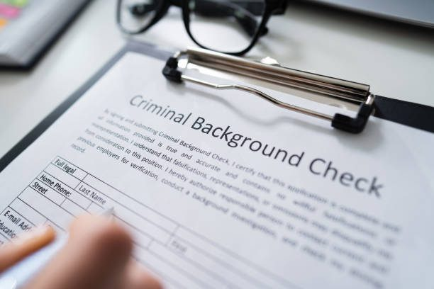 Close-up Of Human Hand Filling Criminal Background Check